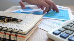 Revisor eller affärsman som kontrollerar finansiella dokument i ett kontor lager videofilmer