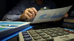 Revisor som använder förstoringsglaset för att kontrollera affärsrapporten Finansiell revision arkivfilmer