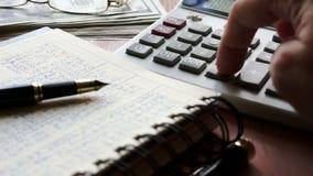 Revisor som använder räknemaskinen för att kontrollera den finansiella rapporten Tabell med legitimationshandlingar stock video