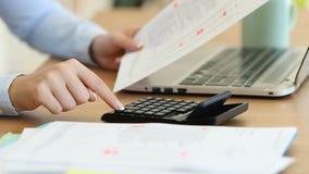 Revisor som beräknar med en räknemaskin på ett skrivbord arkivfilmer