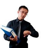 Revisor som rymmer en mapp och håller ögonen på hans klocka Royaltyfri Foto