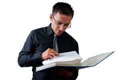 Revisor som söker efter ett dokument på vit Arkivfoto