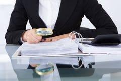 Revisor som undersöker mycket noggrant finansiella dokument Royaltyfria Foton