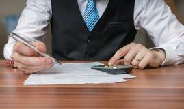 Revisorn eller affärsmannen är beräknande skatter med räknemaskinen Arkivfoto
