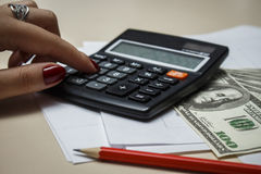 Revisorn räknar pengar med en räknemaskin Fotografering för Bildbyråer