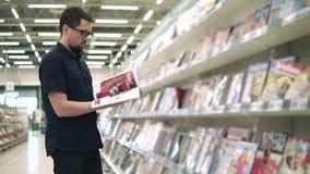 Revista adulta de la lectura del individuo en la tienda almacen de metraje de vídeo