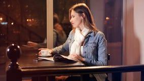 Revista atractiva de la lectura de la mujer en el café 4K almacen de video