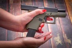 Revista de la arma de mano del cargamento de la mujer Imagen de archivo libre de regalías