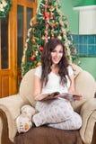 Revista de la lectura de la mujer bastante joven que se sienta en la sonrisa del sofá Fotografía de archivo