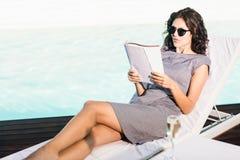 Revista de la lectura de la mujer joven cerca del poolside fotos de archivo
