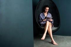 Revista de la lectura de la mujer, sentada en silla de balanceo Fotos de archivo libres de regalías