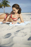 Revista de la lectura del adolescente en la playa Imagen de archivo libre de regalías
