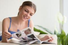 Revista de la lectura de la mujer bastante joven en casa Imágenes de archivo libres de regalías