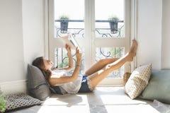 Revista de moda bonita joven de la lectura de la muchacha cerca de la ventana Imagen de archivo