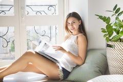 Revista de moda bonita joven de la lectura de la muchacha cerca de la ventana Imagenes de archivo