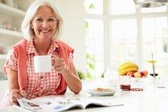 Revista envejecida centro de la lectura de la mujer sobre el desayuno Imágenes de archivo libres de regalías