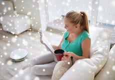 Revista feliz de la lectura de la mujer con la taza de té en casa Imagenes de archivo