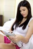 Revista hermosa feliz de la lectura de la mujer en la cama que se relaja Foto de archivo