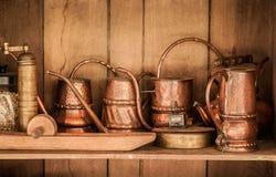 Revista, os potenciômetros do vintage e os frascos velhos de bronze no armário de madeira Imagens de Stock Royalty Free