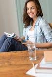 Revista sonriente de la lectura del adolescente en casa Fotos de archivo libres de regalías