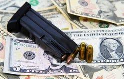 Revista y pistolas del arma en billetes de banco del dólar Fotografía de archivo libre de regalías