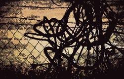 REVOLTIJO ABSTRACTO DEL ALAMBRE CONTRA UNA CERCA foto de archivo libre de regalías