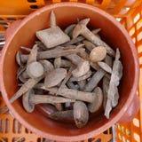 Revoltijo de clavos y de herramientas oxidados viejos de la mano en una caja pl?stica anaranjada fotos de archivo libres de regalías