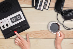 Revolution concept. Retro cassette tape recorder with headphones and cassettes lying on wooden table. View of woman`s hands pressi royalty free stock image