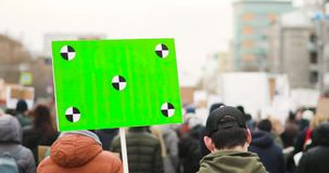Man holds big poster with green screen and walking the street with crowd on city rally, back view.