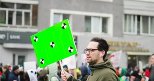 Young independent man holds big poster with green screen and walking the street among crowd on city rally, side view.