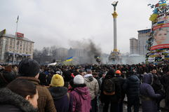 Revolution in Kiev, Ukraine. People taking part in the revolution happening in Independence Square, Kiev, Ukraine with smoke rising in the background royalty free stock photo