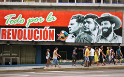 Revolution poster, Havana, Cuba. Cuban people passing by a poster showing the three leaders of cuban revolution
