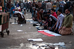 Revolutionaries in Tahrir Square. Revolutionary praying in the streets Stock Image
