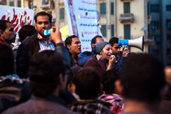 Revolutionaries in Tahrir Square. Revolutionary Woman with megaphone Royalty Free Stock Photo