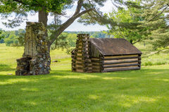 A revolutionary cabin sits beneith a tree at Valley Forge. Royalty Free Stock Images