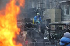 A revolutionary in a helmet on the burning maidan. Ukraine, Kiev. Burning bus action movie with bat. A revolutionary in a helmet on the burning maidan royalty free stock photography