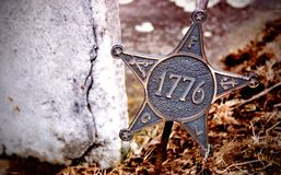 Revolutionary War Star - 1776. Bronze star that sits in the ground by a grave stone. It signifies that the person buried here served in the Revolutionary War in royalty free stock photography