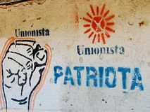 Revolutionist's Sign on the Wall in Guatemala. Protest sign on the wall in Guatemala. Words unionista (unionist) and patriota (patriot), orange symbol of sun and stock photography