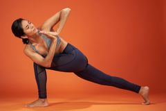 Revolved Crescent Lunge yoga pose. Woman demonstrate on orange color studio background royalty free stock images