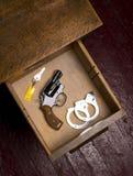 Revolver 38 dans le tiroir de bureau avec des menottes Photos stock