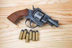 Revolver with ammunition on the table. Revolver with ammunition on the wooden table Royalty Free Stock Photo