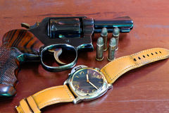 Revolver with bullets on brown wooden tables and clocks. Revolver with bullets and watch Royalty Free Stock Image