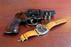 Revolver with bullets on brown wooden tables and clocks. Revolver with bullets on brown wooden tables and watches Royalty Free Stock Photography
