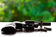 Revolver with bullets on the table. Gun sitting on a table with bullet shells Stock Photo