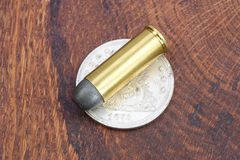 Revolver cartridge and Silver Dollar Wild West period. On wooden background Royalty Free Stock Images