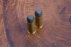 Revolver cartridges .45 Cal Wild West period. On wooden background Royalty Free Stock Photo