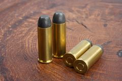 Revolver cartridges .45 Cal Wild West period. On wooden background Royalty Free Stock Image