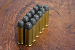 Revolver cartridges .45 Cal Wild West period. On wooden background Royalty Free Stock Photos
