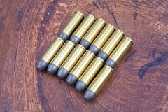 Revolver cartridges .45 Cal Wild West period. On wooden background Royalty Free Stock Images