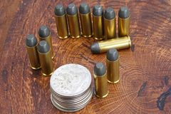 Revolver cartridges and Silver Dollar Wild West period on wooden background Stock Photos